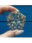 Брошь, усыпанная искристыми кристаллами