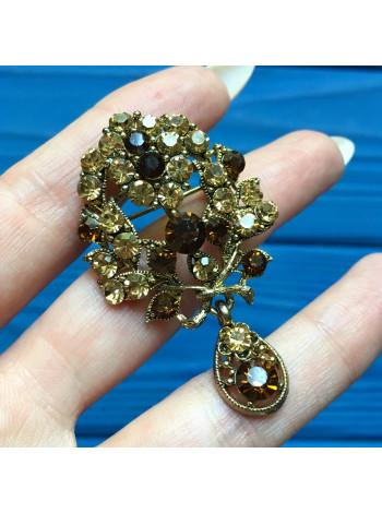 Брошь с кристаллами цвета коньячного бриллианта и подвижной подвеской.