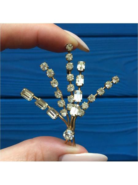 Брошь с кристаллами разной формы, каждый из которых закреплен крапанами (лапками)
